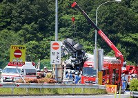 A crane lifts up the car that smashed into the bus near the entrance to the Shinshiro parking area on the Tomei Expressway in Shinshiro, Aichi Prefecture, on June 10, 2017. (Mainichi)