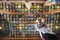 575枚の絵が本堂の天井を埋め尽くす。四国八十八カ所霊場の第三十七番札所、岩本寺(高知県四万十町)。参拝の手を合わせた後、じっと見上げるお遍路さんの姿がある=高知県四万十町で2017年5月30日、山崎一輝撮影
