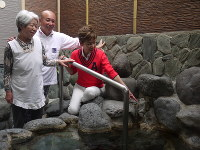 露天風呂にある寿作さんの顔に似ているという「人面石」を指さす初子さん(右)。隣は店主の親光さんと臼田さん=船橋市本中山の「寿湯」で
