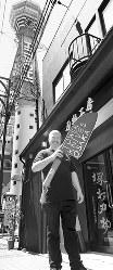 2016年12月にオープンした新しい店舗前に立つ経営者のカナダ人、ビヨン・ハイバーグさん。近くには通天閣がそびえる=大阪市浪速区で、貝塚太一撮影