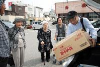 買った品物を段ボール箱に詰め、車に積み込む運転ボランティア(右)=兵庫県相生市大島町で、松田学撮影
