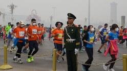 2014年10月の北京国際マラソン。マスク姿の参加者も=中国・北京市の天安門広場付近で工藤哲撮影