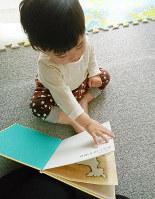 絵本のページをめくる赤ちゃん