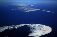 野付半島(手前)のかなたに浮かぶ北方領土・国後島=別海町で2009年3月、本社機から尾籠章裕撮影