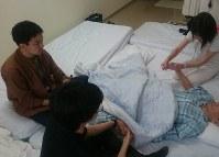 マットが敷き詰められた病室で、家族のマッサージを受ける佐藤さん=神奈川県内で5月21日、照山哲史撮影