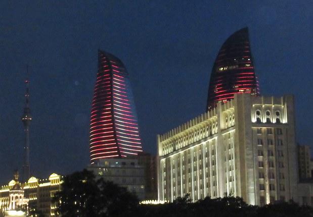 夜の火焔タワー(3本のうち1本は後ろに隠れている)。右側のビルには明かりがあるが左側は真っ暗なように見える