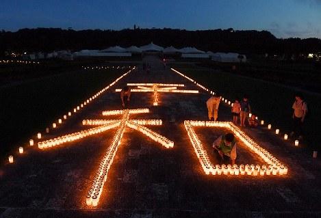 キャンドルに火がともされ、暗がりに浮かび上がる「平和」の文字=沖縄県糸満市の平和祈念公園で2017年6月22日午後7時52分、森園道子撮影