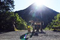 遥拝所から見える日室岳の頂上で輝く太陽=京都府福知山市で、小松雄介撮影
