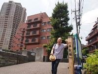 一本松で一息入れる一之輔さん。左手には現代のランドマーク、元麻布ヒルズフォレストタワーがそびえる=東京都港区元麻布で