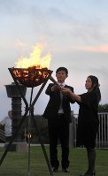 Noriyoshi Oshiro, left, and Yukiko Yamashiro from an association of family members of the war dead light a fire in a brazier during a commemorative event for the Battle of Okinawa, in Itoman, Okinawa Prefecture, on June 22, 2017. (Mainichi)