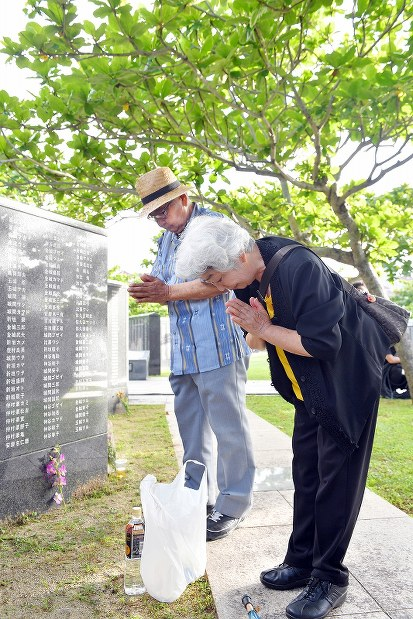 戦没者の名前が刻まれた「平和の礎」の前で、手を合わせて冥福を祈る遺族=沖縄県糸満市の平和祈念公園で2017年6月23日午前6時54分、森園道子撮影