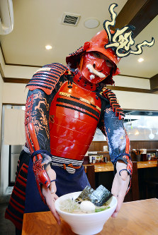 Employee Kojiro Shimizu wears full armor as he delivers a bowl of ramen at the Moiwayama branch of noodle chain Ramen Kabto in Sapporo's Chuo Ward, on June 20, 2017. (Mainichi)