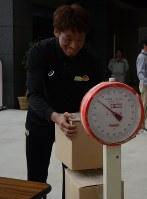 割り箸の重さを量る柳川選手=仙台市青葉区の葛岡リサイクルプラザで