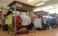 ミサイル落下を想定して机の下で身を守る児童ら=山口県岩国市の通津小学校で2017年6月23日、宮城裕也撮影(画像の一部を加工しています)