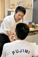 男子生徒と提出物の確認をする担任の福島涼太教諭(奥)=埼玉県熊谷市の熊谷市立富士見中学校で