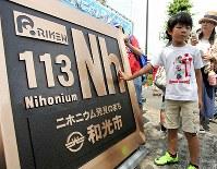 式典会場に仮設置された新元素「ニホニウム」のプレートの感触を確かめる子供たち=2017年6月24日、橋本政明撮影