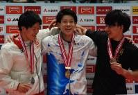 金メダルをかけられ、喜びの表情の武田一志選手(中央)=高崎市下和田町の高崎アリーナで