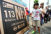 式典会場に仮設置された新元素「ニホニウム」のプレートの感触を確かめる子供たち=和光市丸山台交差点のポケットパークで