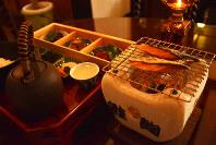 網の上にサケを載せ、あぶってから食べる。テーブル席にはおしゃれなランプが置いてあり、くつろげる雰囲気だ