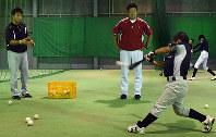トスバッティングに取り組む子どもたち。出口雄大さん(左)や坂田和隆さん(中央)が数球おきにフォームを指摘するなど細かく指導している=福岡県粕屋町で