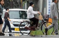 気温が上昇し、自転車のタイヤが路面に溶け込むように見える「逃げ水」現象=滋賀県東近江市で、金子裕次郎撮影