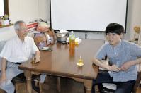 食卓に座り、冷たいお茶を飲みながら雑談する宮本幸一さん(左)と石山資さん=東京都練馬区で