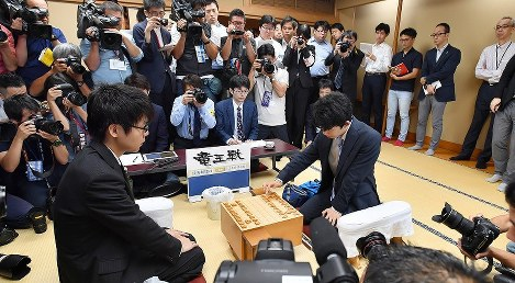 Sota Fujii, right, makes his first move in a game against fellow fourth-dan player Yasuhiro Masuda, at Shogi Hall in Tokyo's Shibuya Ward on June 26, 2017. (Mainichi)