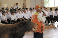 Keiji Sato, in the orange vest, speaks to students about what to do if they encounter a bear, at Sotoasahikawa Junior High School in Akita, on June 26, 2017. (Mainichi)