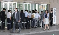 Stockholders line up in front of the venue for the Takata Corp. shareholders meeting in Tokyo's Minato Ward on June 27, 2017. (Mainichi)