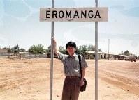 オーストラリアの「エロマンガ」。地名が書かれた看板の前で、満足そうな笑みを浮かべる学生時代の安居さん=1997年11月撮影、安居さん提供