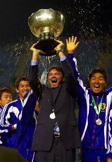 【トルシエ監督=1998~2002年】アジア杯で優勝。カップを誇らしげに掲げるトルシエ監督。選手たちからは祝福の水を浴びせられた=ベイルート・スポーツシティで2000年10月29日、近藤卓資撮影