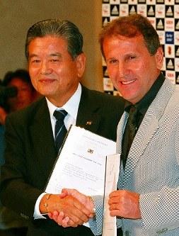 【ジーコ監督=2002~06年】契約書にサイン後、握手を交わす川淵三郎・日本サッカー協会会長(左)とジーコ監督=東京都内のホテルで2002年7月22日、石井諭撮影