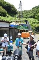 ボーリング調査(奥)に着手し、報道陣の取材に答える中国電の担当者(中央)