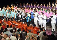 ステージ上と聴衆が一緒に「琵琶湖周航の歌」を大合唱したびわ湖音楽祭のフィナーレ。中央で両手を伸ばしているのが加藤登紀子さん=大津市のびわ湖ホールで、塚原和俊撮影