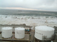In this March 11, 2011 file photo, waves are seen washing over a 10-meter-high breakwater and approaching the Fukushima No. 1 nuclear plant. (Photo courtesy of Tokyo Electric Power Co.)