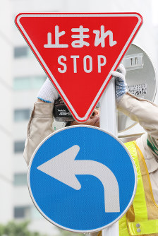 A new stop sign in both Japanese and English is seen being installed in Tokyo's Minato Ward on July 1, 2017. (Mainichi)