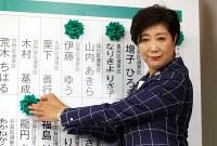 東京都議選で、当選が確実となった候補者の名前に緑色の花をつける小池百合子都知事=東京都新宿区で2017年7月2日午後8時3分、小川昌宏撮影