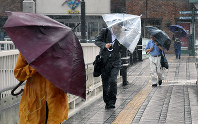 Commuters slant their umbrellas to keep out the driving rain near JR Nagasaki Station on the morning of July 4, 2017. (Mainichi)