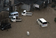 Houses and cars are seen flooded in the Fukuoka Prefecture city of Asakura at around 6:30 p.m. on July 5, 2017. (Mainichi)