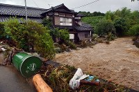 A muddy stream of flood water from heavy rain flows into a house along a river in Asakura, Fukuoka Prefecture, on July 5, 2017. (Mainichi)