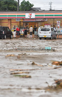 People wait for the weather to change in front of a convenience store with a flooded parking lot in Asakura, Fukuoka Prefecture, on the morning of July 6, 2017. (Mainichi)