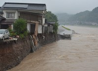 One corner of a house hangs over the swollen Kagetsu River in Hita, Oita Prefecture, on the morning of July 6, 2017, after the riverbank was eroded by the fast-moving waters. (Mainichi)