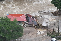 In this photo taken from a Mainichi Shimbun helicopter, a house is surrounded by muddy floodwater from the Hikosan River in the town of Soeda, Fukuoka Prefecture, on July 6, 2017. (Mainichi)