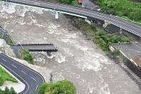 In this photo taken from a Mainichi Shimbun helicopter on July 6, 2017, a section of a bridge in Hita, Oita Prefecture, has been swept away by floodwaters. (Mainichi)