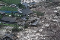 In this photo taken from a Mainichi Shimbun helicopter, houses are buried in mud from a large landslide in Hita, Oita Prefecture, on July 6, 2017. (Mainichi)