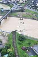 In this photo taken from a Mainichi Shimbun helicopter on July 6, 2017, a steel bridge on the JR Kyushu Kyudai Main Line has been washed away by floodwaters in Hita, Oita Prefecture. (Mainichi)