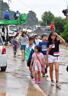 Children who had evacuated to Masue Elementary School in Asakura, Fukuoka Prefecture, walk along a road covered in mud and floodwater, on July 6, 2017. (Mainichi)
