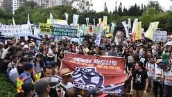 「中国政府に抗議する」などと書いた横断幕を手にデモ行進する市民ら=香港・銅鑼湾のビクトリア・パークで2017年7月1日、福岡静哉撮影