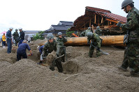 A team including Self-Defense Forces members searches for missing people in Asakura, Fukuoka Prefecture, on July 7, 2017. (Mainichi)