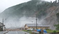 Sections of a mountain on the right collapse and clouds of dust rise into the sky during a landslide in Hita, Oita Prefecture, on July 6, 2017. (Photo courtesy of a local resident)